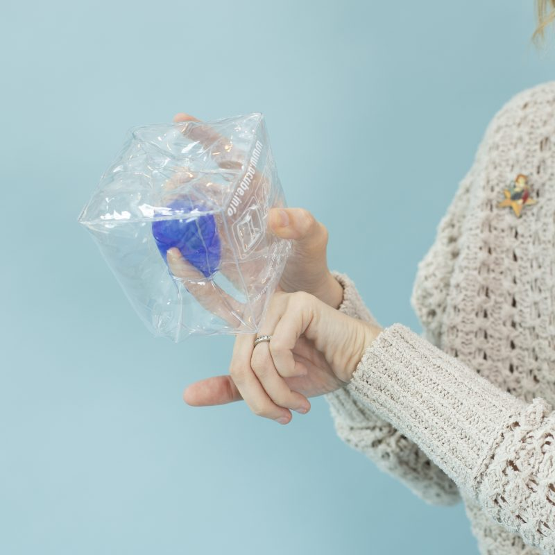 Image of a person holding a clear cube with a cup in it and pressing a finger alongside the cup as if in a vaginal canal.